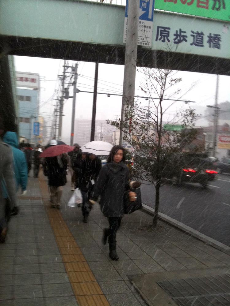 雪の降る中家路を急ぐ人々