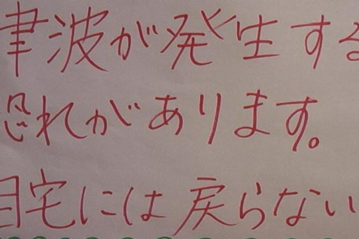 掲示板に張り出された紙「津波注意」