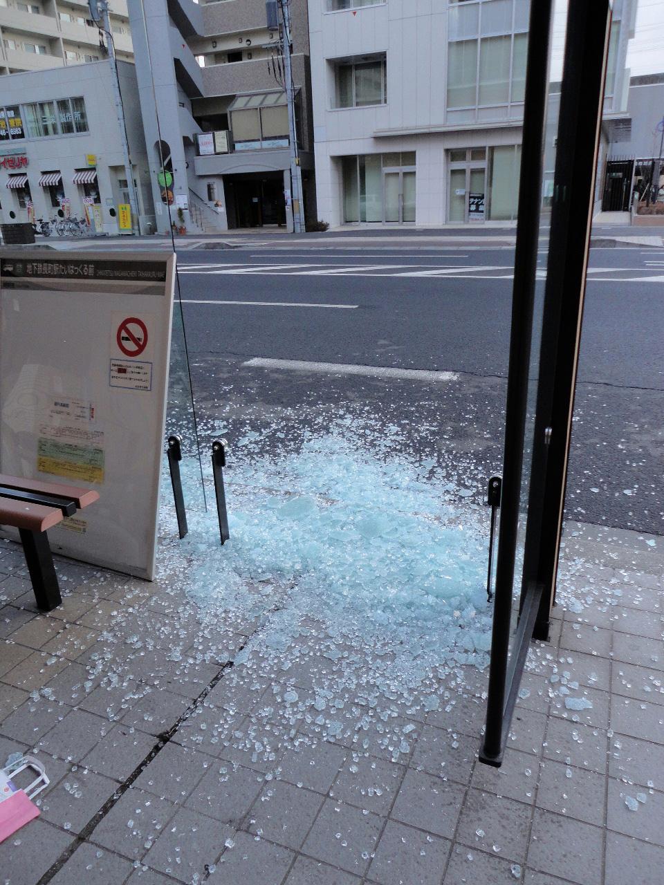 粉々に砕けたバス停のガラス
