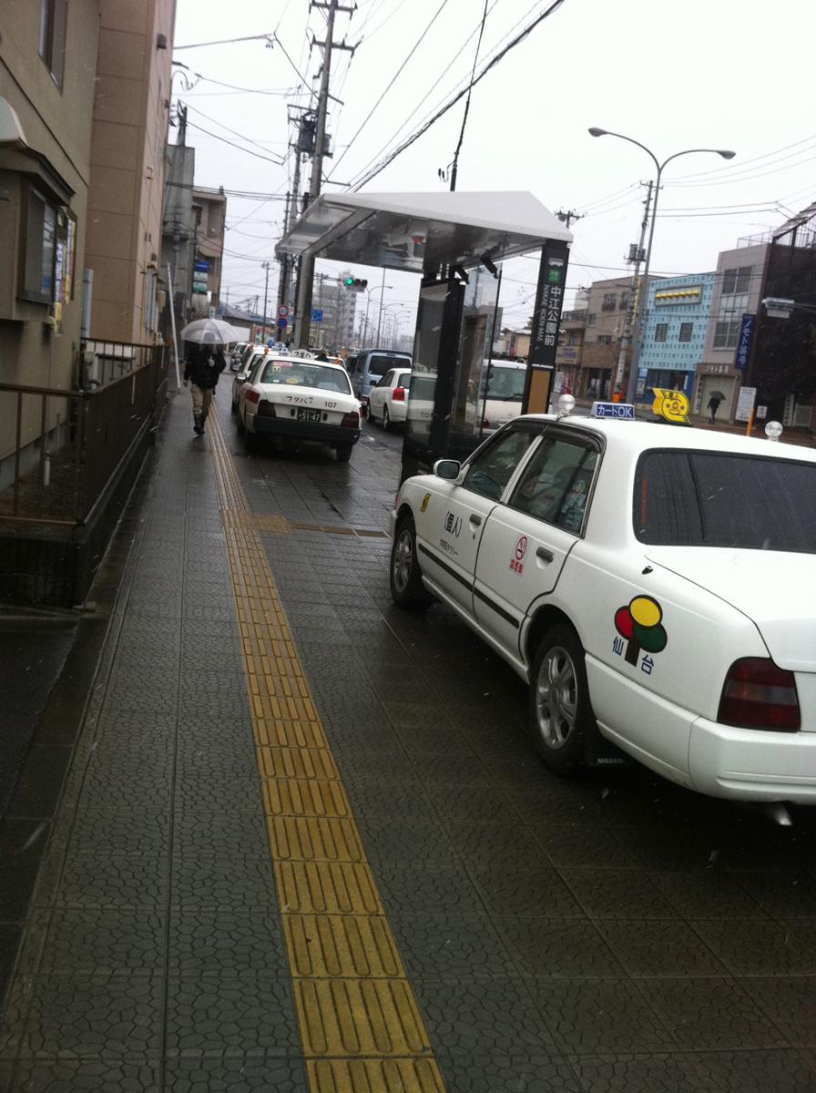 歩道に乗り上げて給油を待つタクシーの列