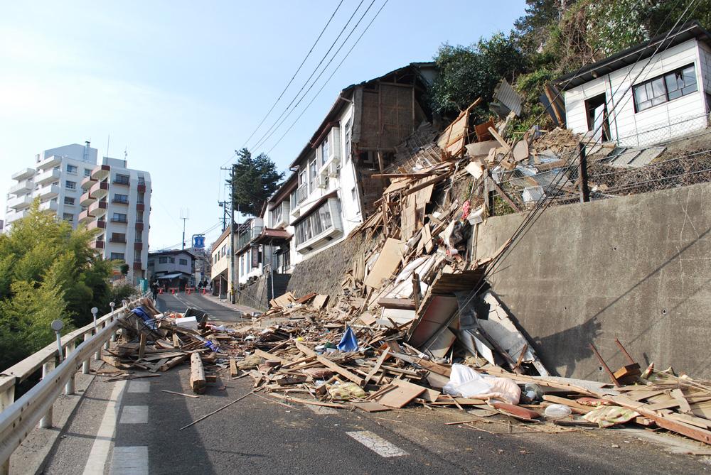 崩落した建物の瓦礫が道路を塞いでいる鹿落坂