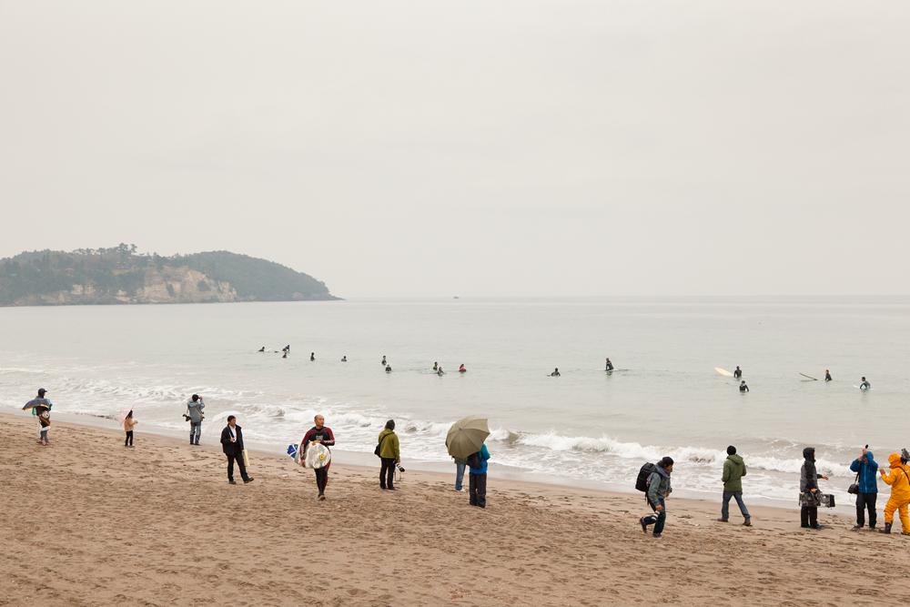 浜から様子を見る人々