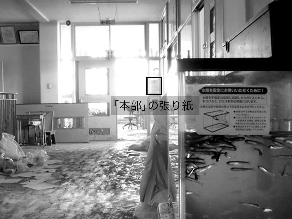中野小学校_13-2_津波で2階も浸水したが七北田川に放流予定のサケの稚魚は無事だった。職員室入り口のガラスに「本部」の張り紙がみえる。